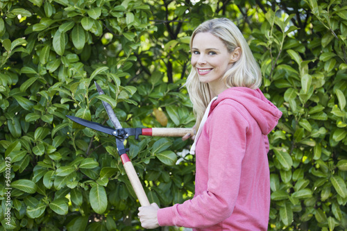 A young woman trimming a hedge with shears