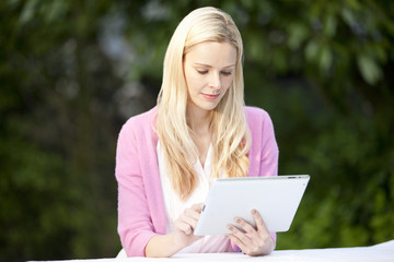 A young blond woman in a garden using a digital tablet