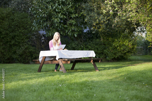 A young blond woman in the garden using a digital tablet