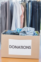 Donations box full of clothes in front of clothes rail