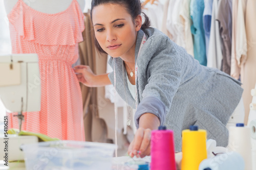 Beautiful fashion designer fixing dress