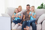 Cute twins and parents watching television