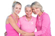 Embracing women wearing pink tops and ribbons for breast cancer