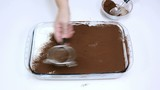 Dusting cocoa top layer of tiramisu cream