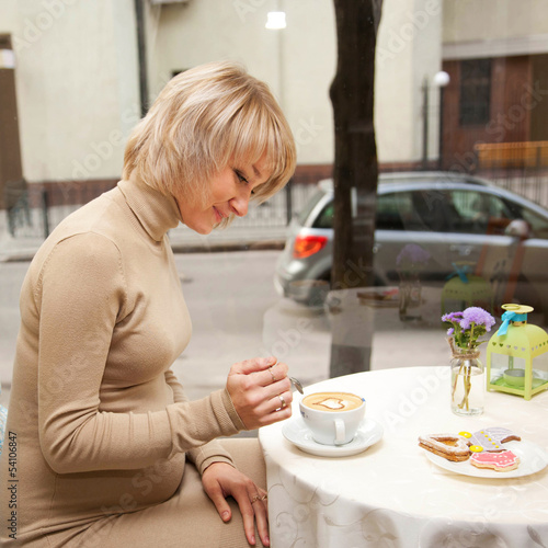 pregnant woman having breakfast cappuccino and cookies