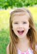 Portrait of screaming little girl in a meadow