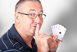 Man with four aces holding finger to mouth