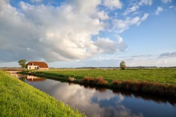 charming farmhouse, river and blue sky