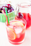 Delicious sweet berry juice of cherry in glass and carafe