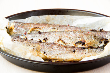 Tasty dish is baked in a pan rainbow trout with onions and spice