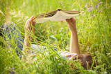 girl reading a book lying in the tall grass - 54110023