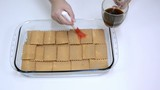 Brushing biscuits with black coffee in glass tray