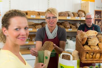 kundin kauft beim biobäcker ein