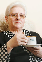 A woman with a pleasant smile enjoying a cup of tea.