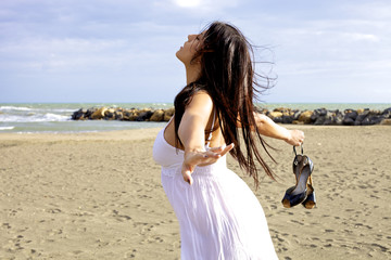 Woman dancing on the beach with eyes closed and wind blowing