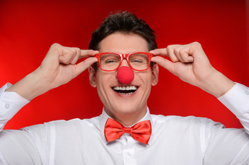 Clown in eyeglasses. Cheerful man with clown nose touching his e