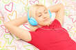 Young female lying on a bed and listening music
