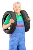 Mechanic holding a vehicle tires and looking at camera