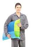 Smiling guy in pajamas holding a pillow