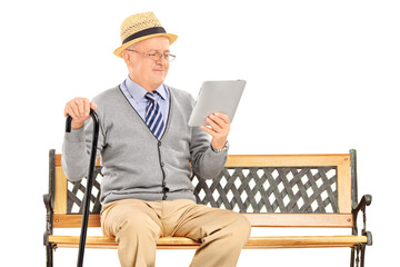 Senior man sitting on a wooden bench and reading from a tablet