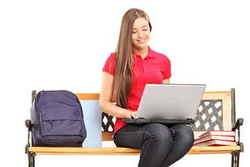 Smiling female student sitting on a wooden bench