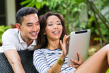 Asian couple outdoor with a tablet pc