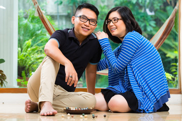 Asian couple at home playing with marbles
