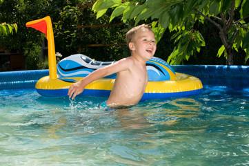 Junge badet im Pool mit Schlauchboot