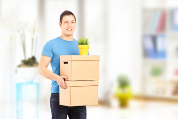 Smiling guy carrying removal boxes during moving
