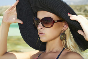 Beautiful blond woman in black hat on a beach