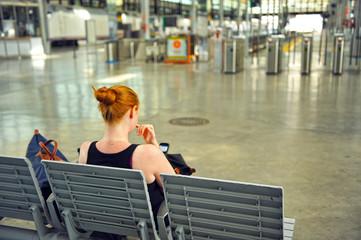 Mujer joven pelirroja en la estación esperando el tren