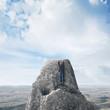 businessman scaling a rock