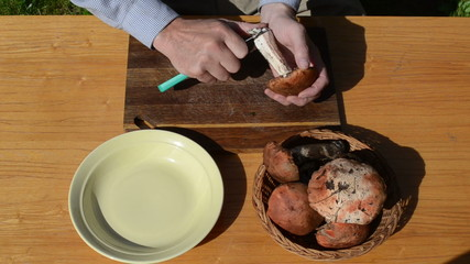 man hands clean red cap mushrooms stipe with knife wooden table