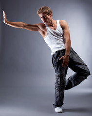 Young handsome hip hop dancer posing in studio