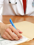 Hands of a doctor filling RX prescription, documents at the desk