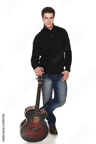 Handsome casual man in full length standing with acoustic guitar
