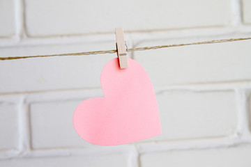 heart with clothespin on white background wall