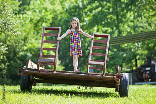 Young girl standing on trailor in a farm field