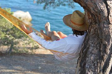 Man in hat in a hammock on pine tree in Crimea a summer day