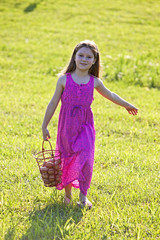 Young girl carrying brown eggs in a basket