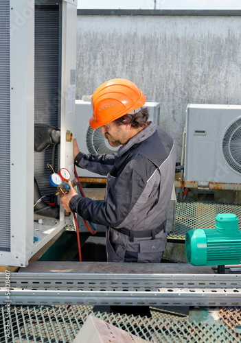 Air Conditioning Repair, repairman on the roof fixing