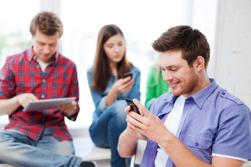 student looking into smartphone at school