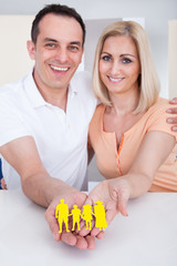 Portrait of happy couple holding family figure cut-out