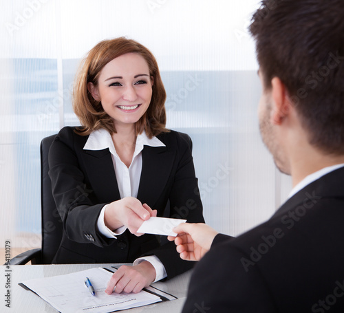Two businesspeople exchanging visiting card
