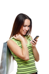 Girl calling by mobile phone with shopping bags. Isolated
