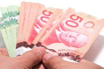 Hand holding a series of Canadian banknotes