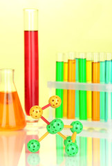 Molecule model and test tubes with colorful liquids