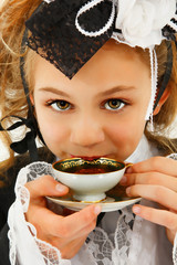 Beautiful Tween Girl in Cosplay Fashion Sipping Tea
