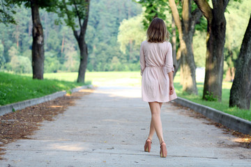 Beautiful young woman walking on the summer park