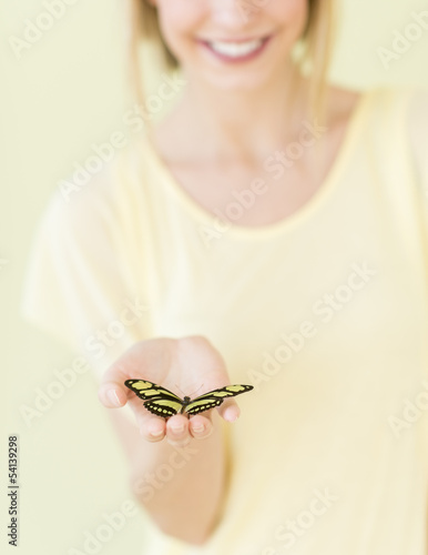 Close-Up Of Young Woman Holding Butterfly In Palm